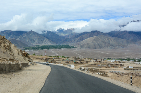 Cars run on mountain road in Ladakh, India. Ladakh is one of the most sparsely populated regions in Jammu and Kashmir.