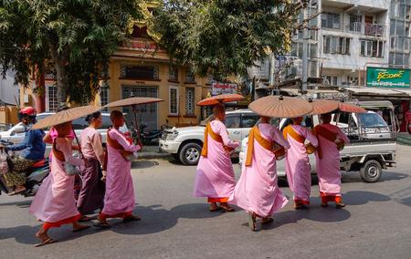 Mandalay, Myanmar - Feb 21, 2016. Buddhist nuns walking for morning alms at downtown in Mandalay, Myanmar.