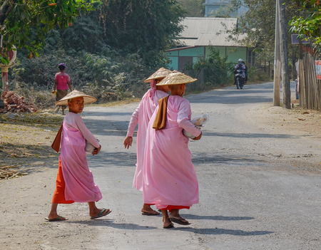 Mandalay, Myanmar - Feb 21, 2016. Buddhist nuns walking for morning alms at countryside in Mandalay Myanmar.