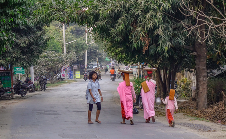 Mandalay, Myanmar - Feb 10, 2017. Buddhist nuns walking for morning alms at countryside in Mandalay, Myanmar.