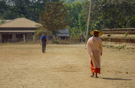 A Buddhist nun walking for morning alms at countryside in Mandalay, Myanmar.