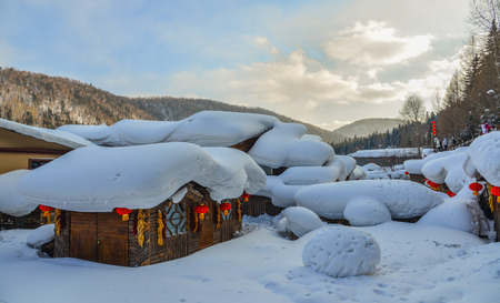 Wooden houses covered by snow at mountain village in Harbin, China.