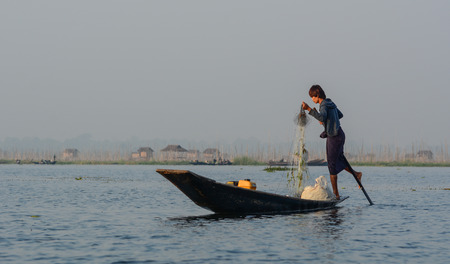 Inle, Myanmar - Feb 14, 2016. Burmese man using the unique methods of rowing and catching fish on Inle Lake. Inle is one of the highest lake at an elevation of 880m.