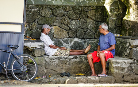Grand Baie, Mauritius - Jan 11, 2017. Old men sitting and chatting in Grand Baie, Mauritius. Mauritius is known for its beaches, lagoons and reefs.