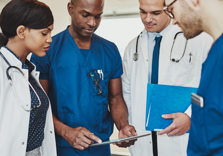 Group of multiracial doctors standing consulting patient records on a tablet computer, close up view