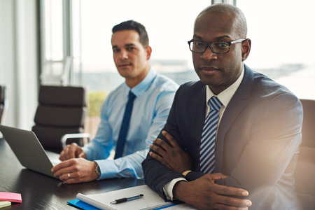 Successful multiracial business partners in a meeting together with a young Hispanic man using a laptop and African American man sitting with folded arms looking at the camera