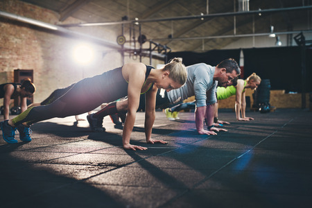 Group of adults doing push up exercises at indoor physical fitness cross-training exercise facility with bright light flare over them