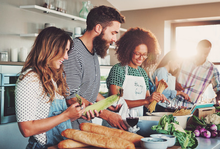 Photo pour Good friends laughing and talking while preparing meals at table full of vegetables and pasta ready for cooking in kitchen - image libre de droit