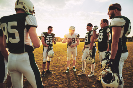 Photo pour Young American football quarterback discussing offensive plays with his teammates during a practice session outside on a sports field in the afternoon - image libre de droit