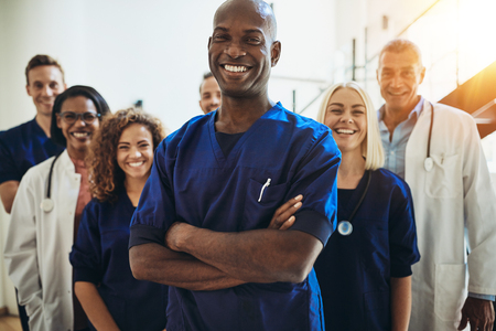 Photo pour Young African male doctor smiling while standing in a hospital corridor with a diverse group of staff in the background - image libre de droit