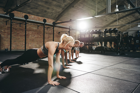 Photo for Diverse group of fit people in sportswear doing pushups together on a gym floor during a workout session - Royalty Free Image
