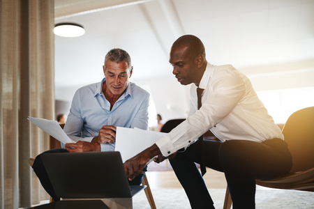Photo pour Two diverse businessmen discussing a project over a laptop while sitting together in a modern office - image libre de droit