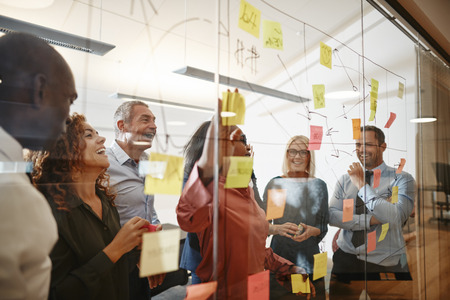Photo for Young African businesswoman and her diverse team laughing while having a brainstorming session with sticky notes  on a glass wall in a modern office - Royalty Free Image
