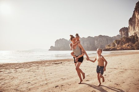 Photo for Laughing mother piggybacking her little daughter while running with her son along a sandy beach during summer vacation - Royalty Free Image