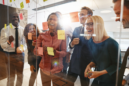 Photo for Laughing group of diverse businesspeople having a brainstorming session together with sticky notes in an office - Royalty Free Image