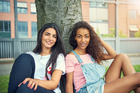 Photo pour Pair of beautiful young adult women sitting next to each other under tree near urban apartment building outdoors - image libre de droit