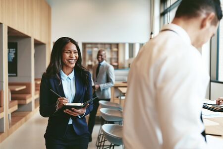 Photo pour Laughing African American businesswoman walking in an office and writing notes after a meeting with colleagues - image libre de droit