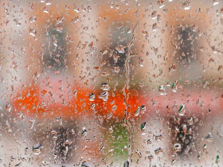 Rain drops on glass window. The cityscape outside the window in a blur. The bokeh effect.