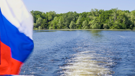 Russian flag on the stern of the ship. Waves and wakes on the water. River or lake on a summer day. Blue sky. Green vegetation on the banks