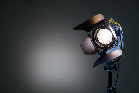 Foto de Floodlight with halogen lamp and Fresnel lens on a gray background. Lighting equipment for shooting. Filming and photographing in the interior. - Imagen libre de derechos