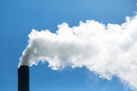 Foto de White smoke comes from the chimney on the background of blue sky. Air pollution and the environment. The greenhouse effect. Environmental disaster - Imagen libre de derechos