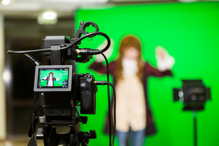 Photo for The actor starred in the interior on a green background. The chroma key. Filming equipment. - Royalty Free Image
