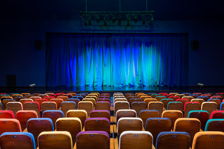 Foto de The auditorium in the theater. Blue-green curtain on the stage. Multicolored spectator chairs. Lighting equipment. - Imagen libre de derechos