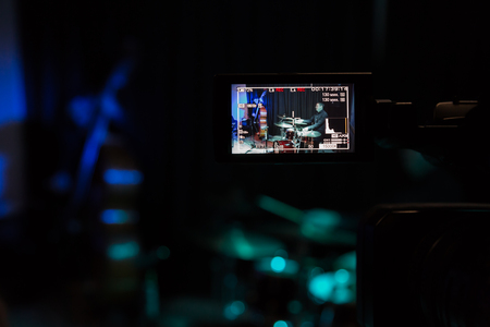 LCD display on the camcorder. Filming of the concert. Musicians playing the double bass and drums