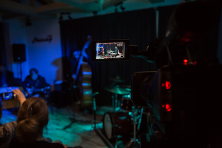 LCD display on the camcorder. Filming of the concert. The musicians play guitar, bass and drums.