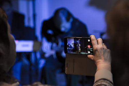 Video shooting with your smartphone. Filming of the concert. Musicians playing the double bass and electric guitar.