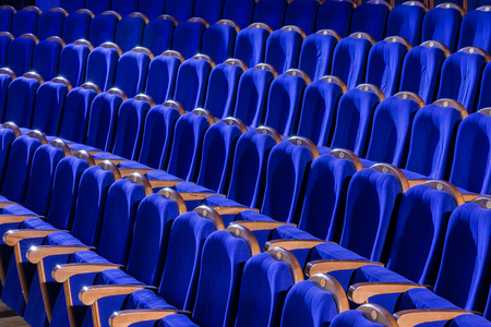 Blue plush chairs with wooden armrests in the auditorium. Empty auditorium in the theater.