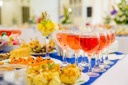 Photo pour Pink wine in glasses. Festively laid tables at the Banquet. Various delicacies, snacks and drinks. Catering. - image libre de droit