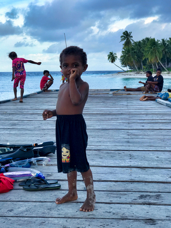 WEST PAPUA, RAJA AMPAT - August 28, 2017: asian child with fingers in the nose  playing with others children on a wooden pier  in Fam island, Raja Ampat archipelago