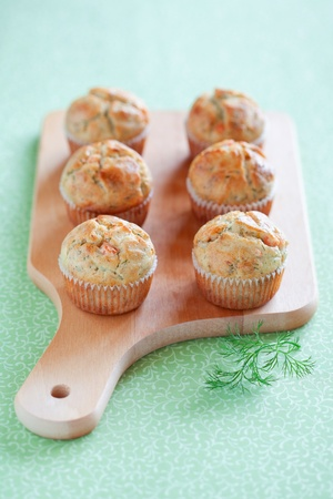 Savoury muffins with salmon and dill on wooden board, selective focus