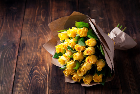 Photo for Yellow roses bouquet in kraft paper on a wooden background, selective focus - Royalty Free Image