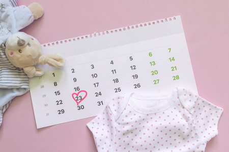 Foto de Set of newborn accessories in anticipation of  child - calendar with circled number 23 (twenty three), baby clothes, toys on pink background. Flat lay, top view. - Imagen libre de derechos