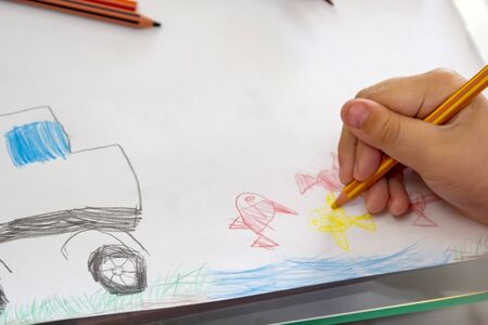 Photo pour Child draws with colorful pencils. Children's drawing on theme of fishing with goldfish, car - image libre de droit