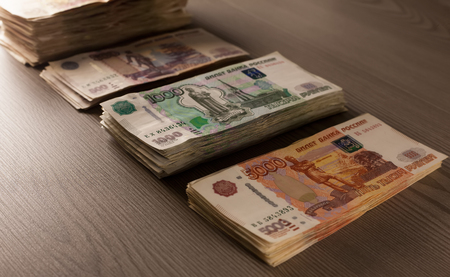 Money. Russian rubles on a wooden background. Bundles of money