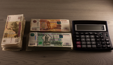 Money. Russian rubles and calculator on a wooden background. Bundles of money
