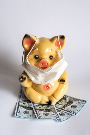 Photo for Piggy bank with protective mask against coronavirus virus affects finances. NCOV-19 affects the economy - Royalty Free Image
