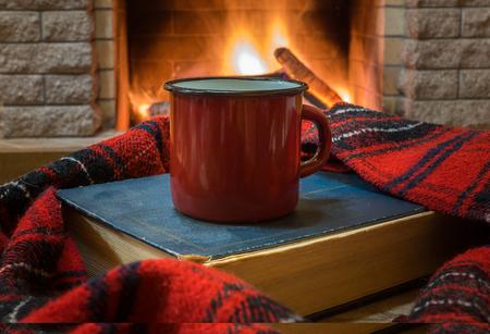 Foto de Big enameled mug with tea, and warm wool scarf , a book , near cozy fireplace, in country house, winter vacation. - Imagen libre de derechos
