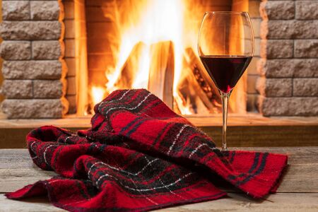Photo for Glass of red wine and warm scarf against cozy fireplace background, in country house, horizontal, hygge , home sweet home. - Royalty Free Image