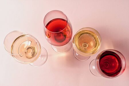 Photo pour Flat lay. A set of rose and white wine in a glasses on pink background, toned in pink. - image libre de droit