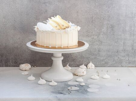 Elegant white cake decorated with melted white chocolate, meringues, waffle paper and macaroons.
