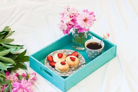 Breakfast in bed with cottage cheese pancakes, fresh strawberries, peonies and cup of coffee. White background.