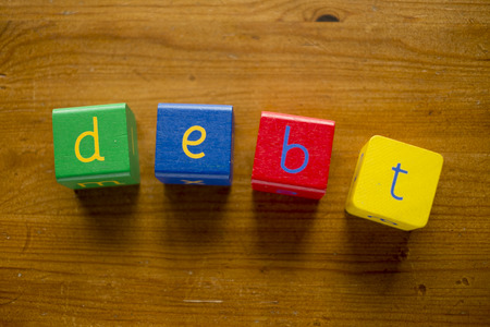 Colorful wooden blocks spelling the word DEBT