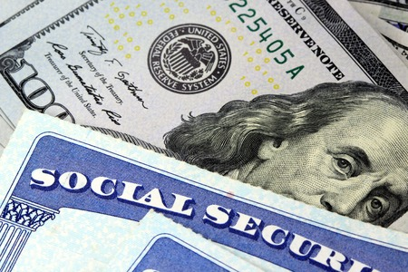Social security card and US currency one hundred dollar bill Retirement Concept Social Security Benefits