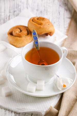 Cup of tea with sugar and cinnamon buns served on white wooden table