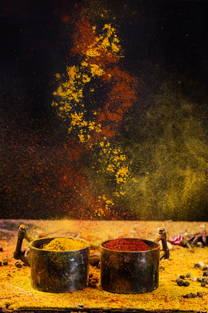 Photo for Spiral mixing of  spices red pepper and turmeric from vintage metal cups over black background. Concept. - Royalty Free Image