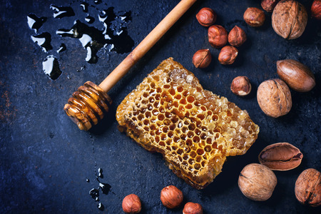 Honeycomb with honey dipper and mix of nuts over dark blue surface. Top view. See series
